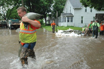 Responders working to hold back flooding with sandbags