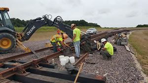 Workers construct new rail spur to facilitate shipping raw materials to manufacturing and distribution center.